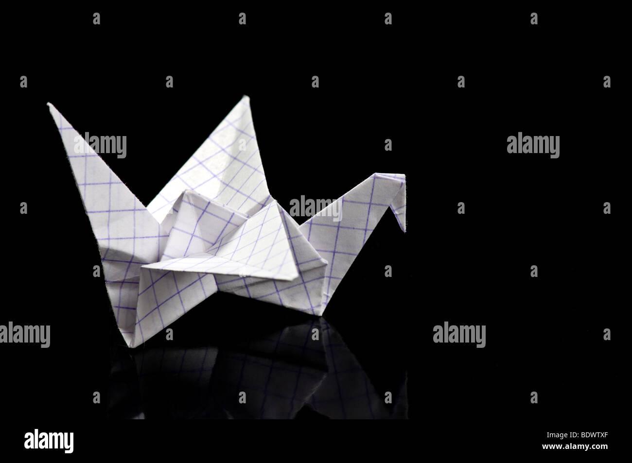 Origami-Kranich auf schwarzem Hintergrund Stockbild