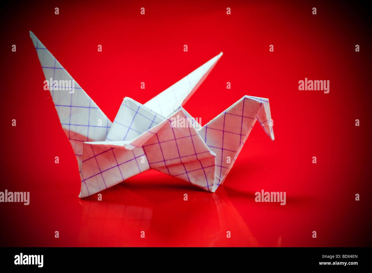 Ein Origami-Papier-Kran auf rotem Grund Stockbild