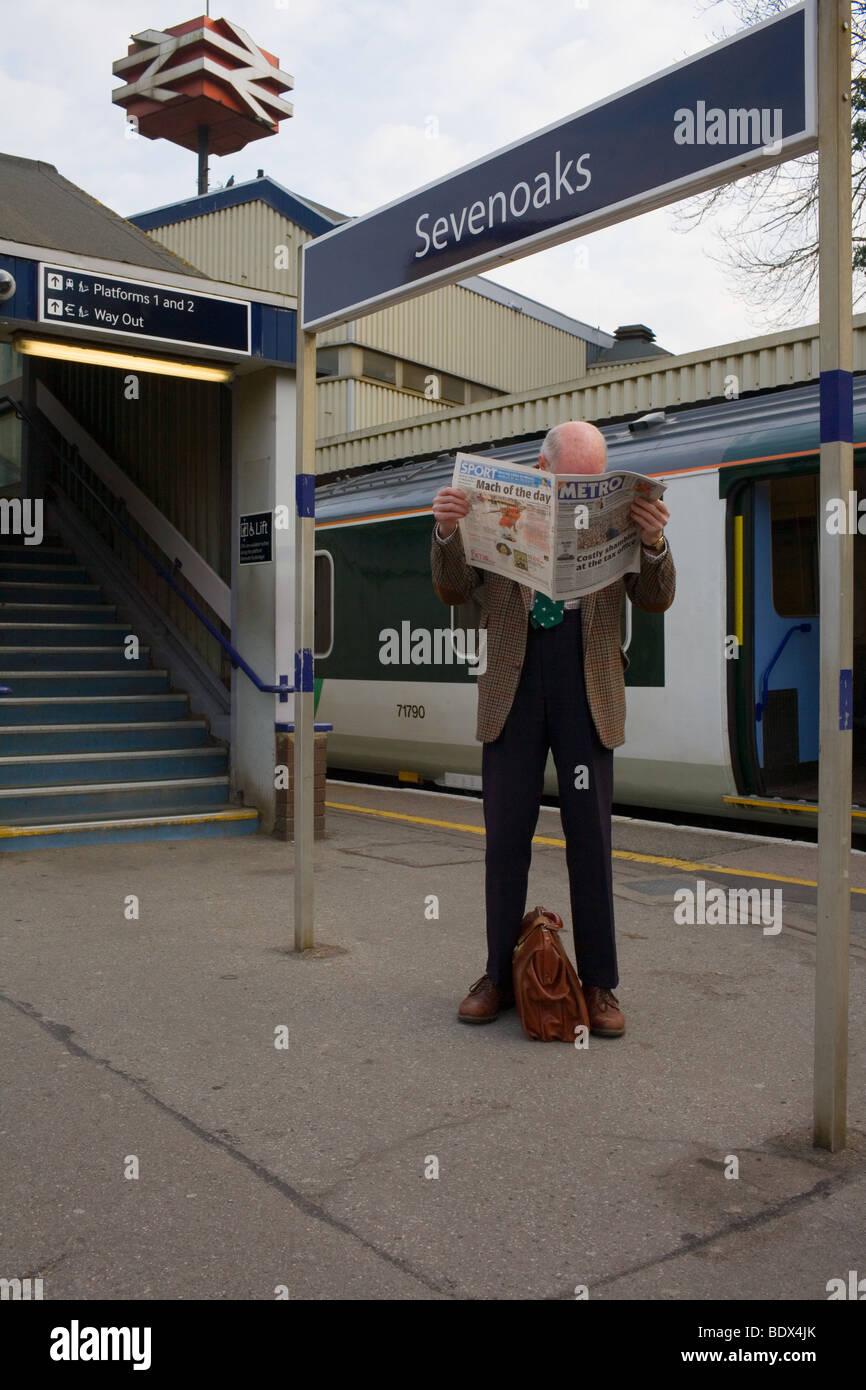 Ein elegant gekleideter älterer Mann liest Zeitung warten auf einen Zug auf einem Bahnsteig. Stockbild