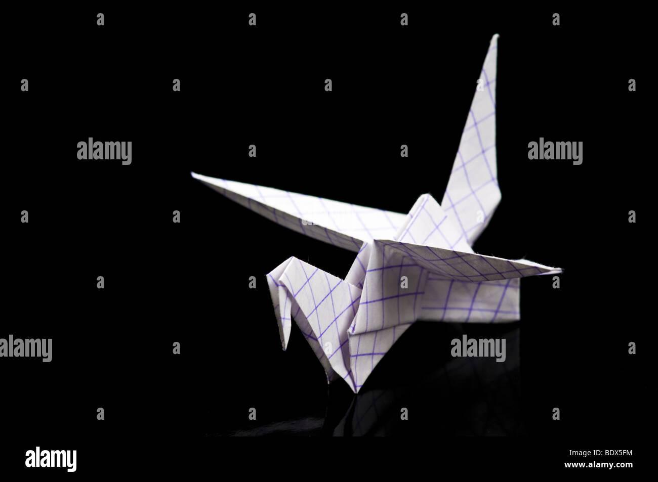 Ein Origami-Papier-Kran über schwarz Stockbild