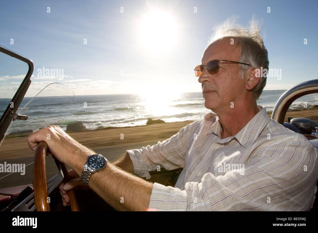 Älterer Mann fahren Sportwagen am Meer Stockbild