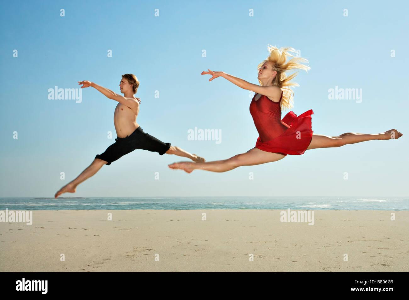 Tänzer an einem Strand springen Stockfoto