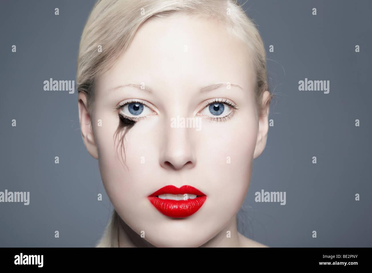 Portrait einer jungen blonden Frau mit Verschmiertem eyeliner mit Blick auf den Betrachter, unvollkommen, Schönheit Stockbild