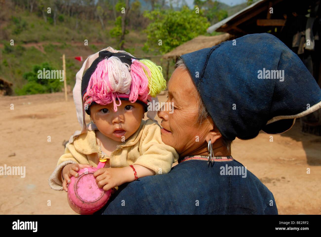 Armut, Portrait, Ethnologie, Yao Frau gekleidet in traditioneller Tracht mit einem Baby im Arm, Dorf Ban Houeyyoum Stockbild