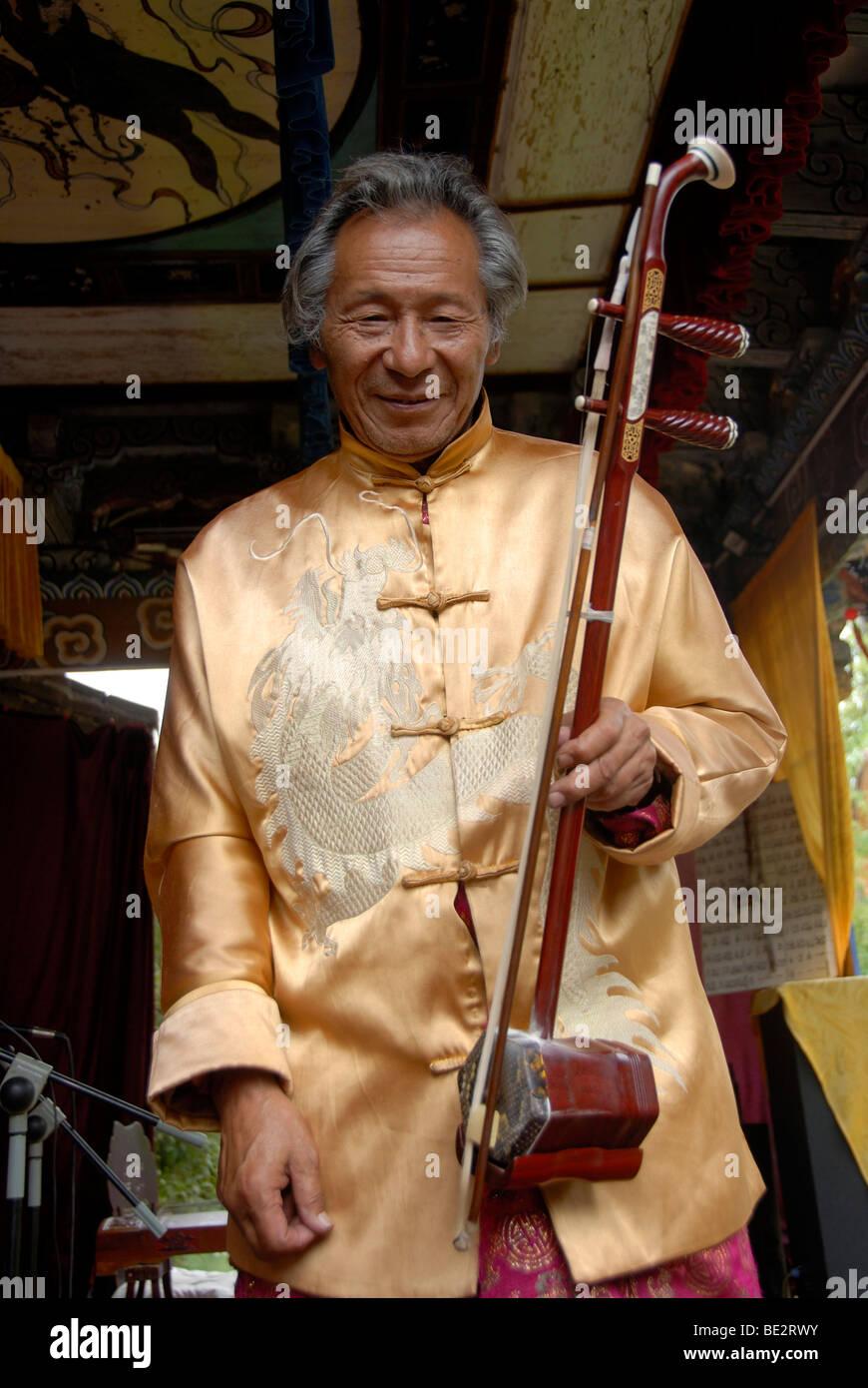 Naxi Musiker, Halloween, Mann mit String instrument, Lijiang, UNESCO-Weltkulturerbe, Provinz Yunnan, Volksrepublik Stockbild