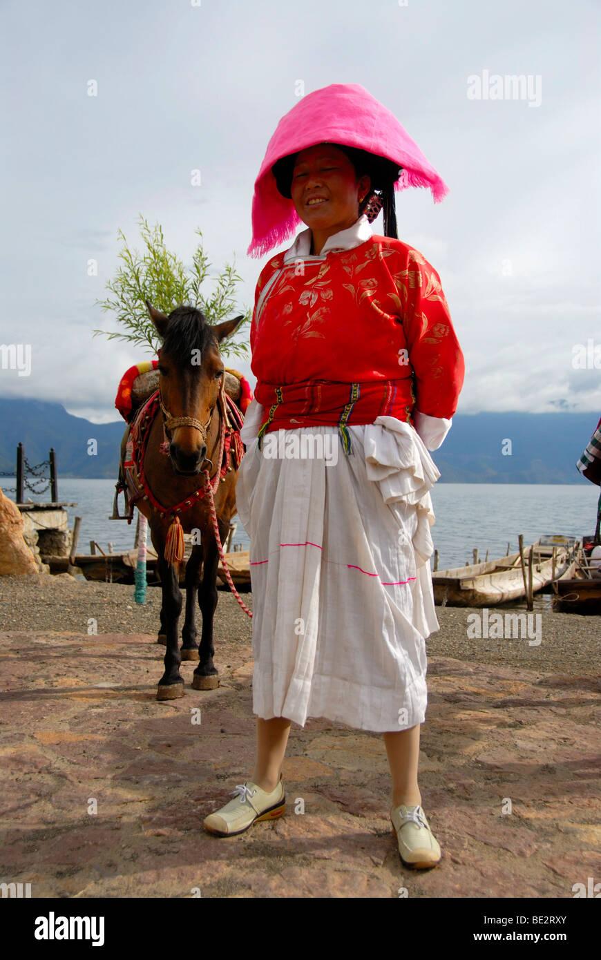 Ethnologie, Frau von der Ethnie Mosu gekleidet in traditioneller Tracht mit Pferd, Luoshui, Lugu Hu See, Provinz Stockbild