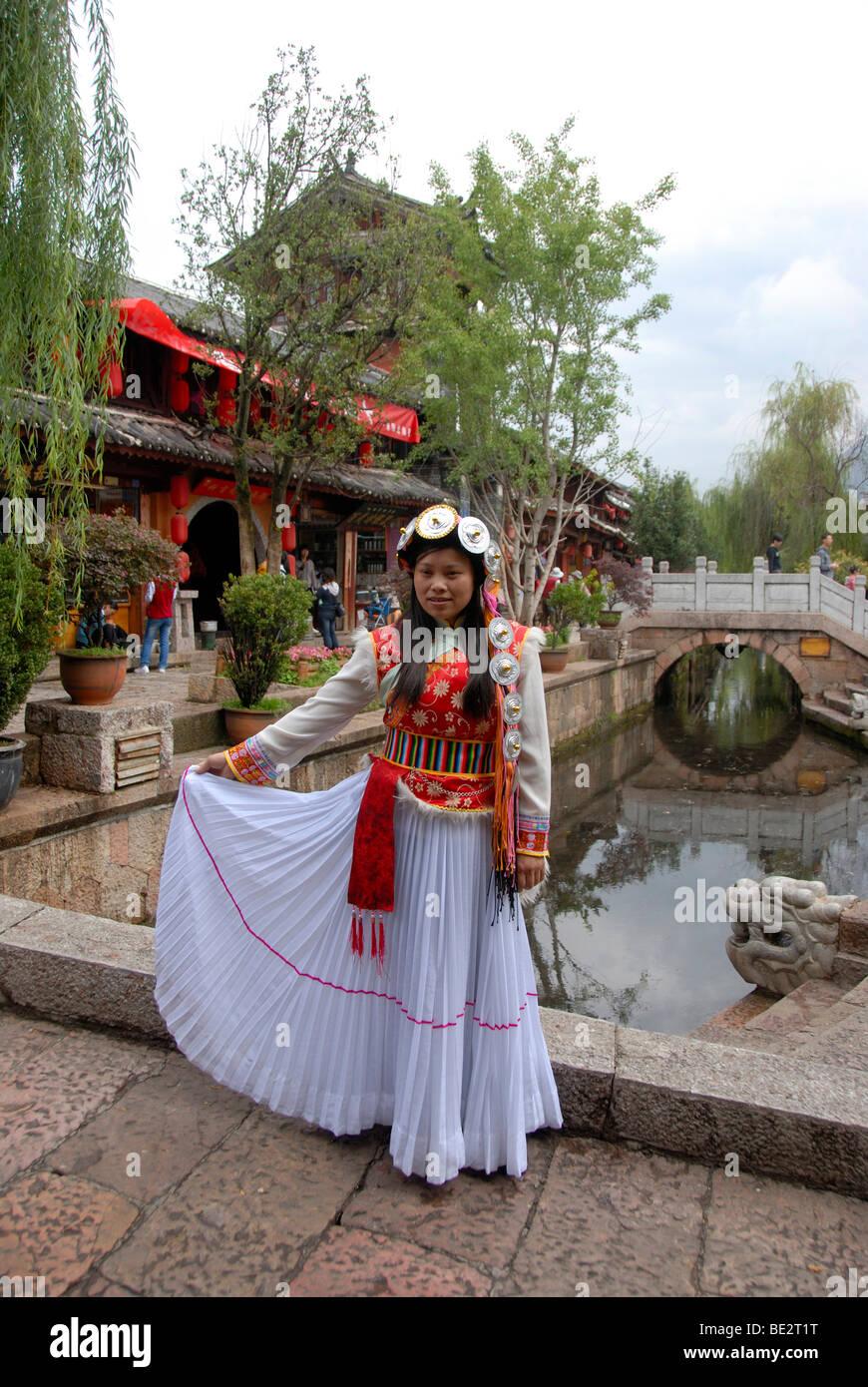 Junge Frauen in einem bunten Kleid auf einer Brücke vor dem alten Markt Platz, historischen Zentrum, Lijiang, Stockbild