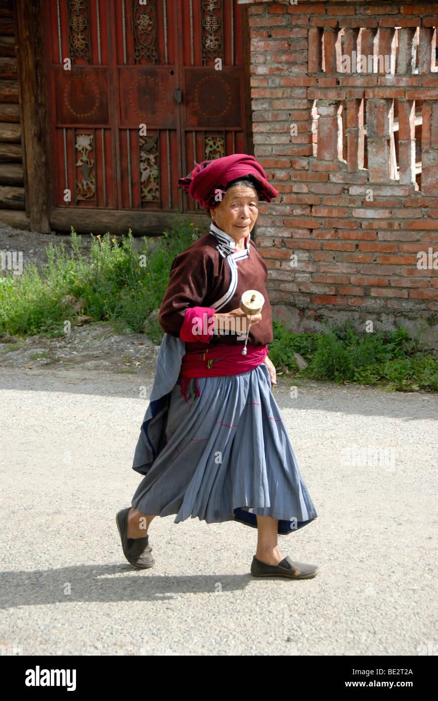 Tibetischen Buddhismus, Ethnologie, Frau von der Ethnie Mosu gekleidet in traditionellen Kostümen eine Gebetsmühle, Stockbild