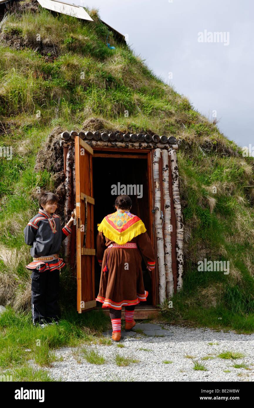 Trägerin der Tracht der Sami People vor ihrer Erde bedeckt Lodge, Hammerfest, Norwegen, Scandinavia, Stockbild