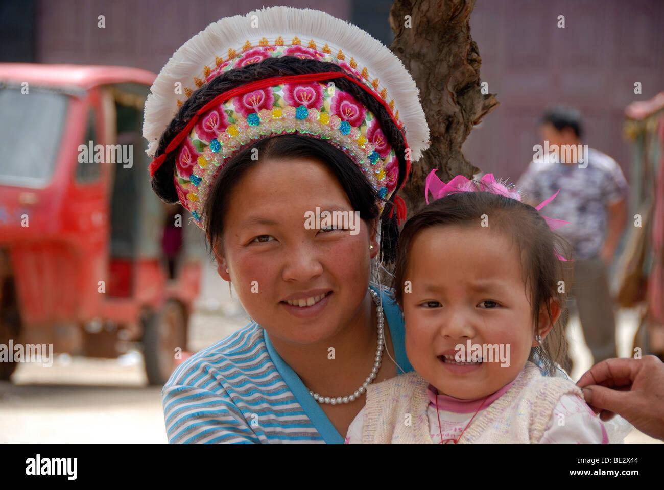 Porträt, Ethnologie, Frau der Volksgruppe Bai mit typischer Kopfbedeckung und ein Kleinkind, Yongning, Lugu Stockbild
