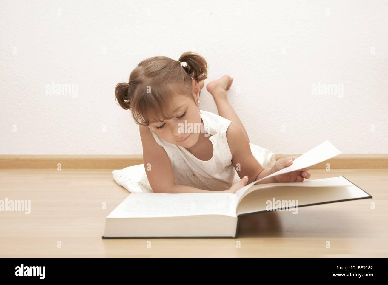 Sechs-jährigen Mädchen ein Buch zu lesen Stockbild