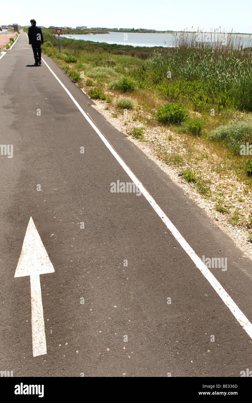 Mann im dunklen Anzug Spaziergänge entfernt sich Küstenweg mit weißer Pfeil auf sie gekleidet Stockbild