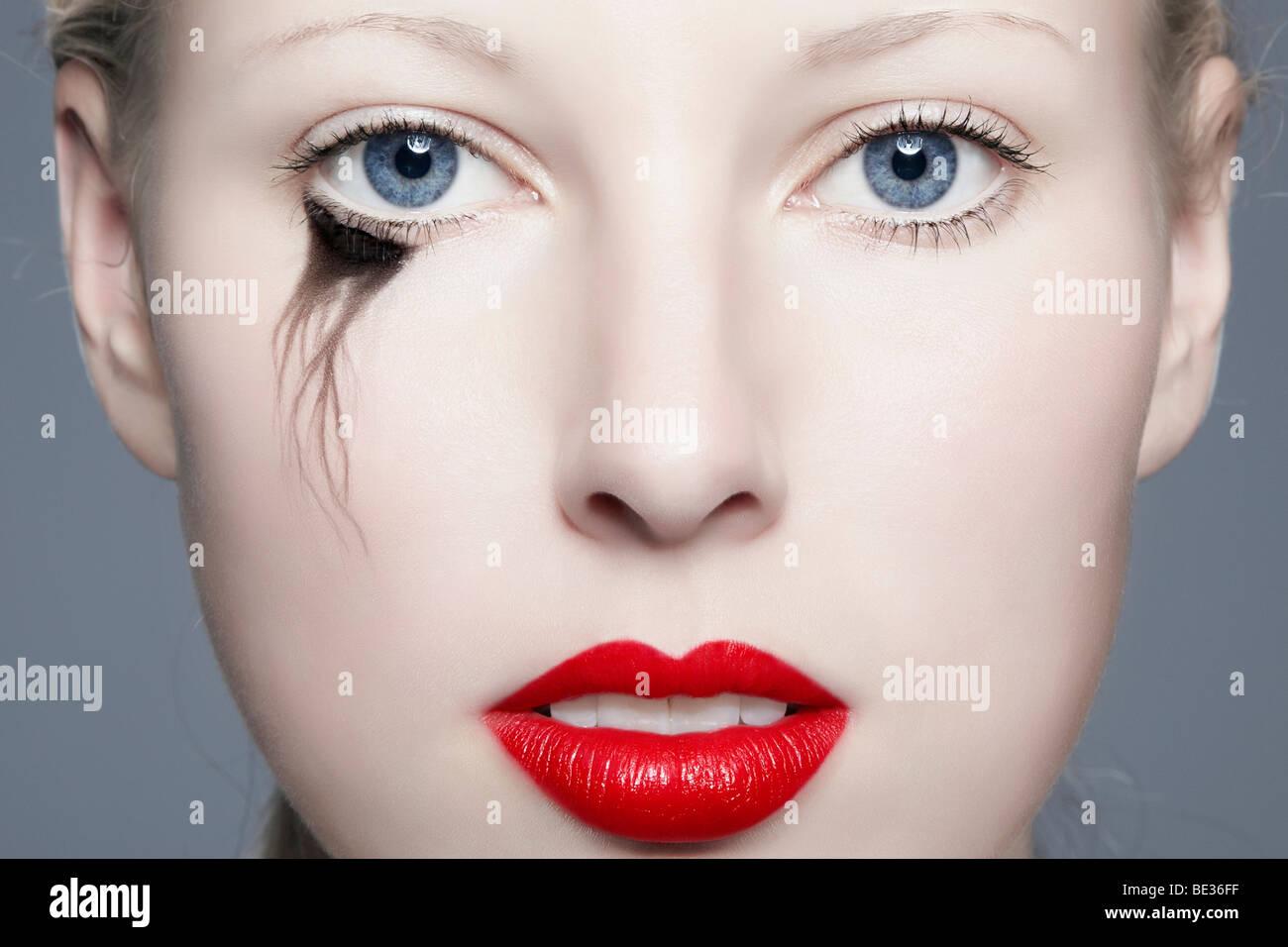 Porträt einer jungen blonden Frau mit verschmierten Eyeliner mit Blick auf den Betrachter, unvollkommen, Schönheit Stockbild