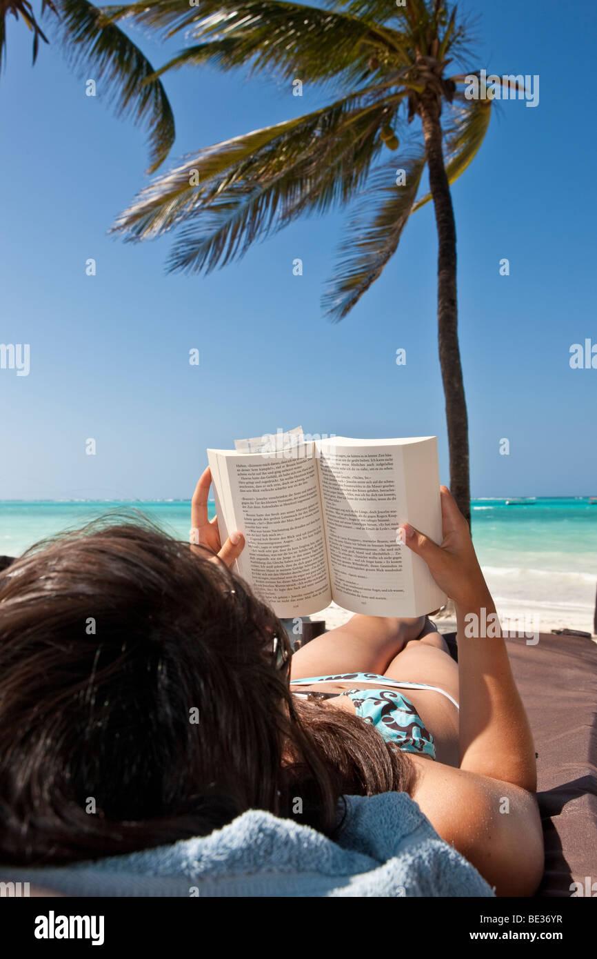 Junge Frau am Strand ein Buch unter Palmen Stockbild