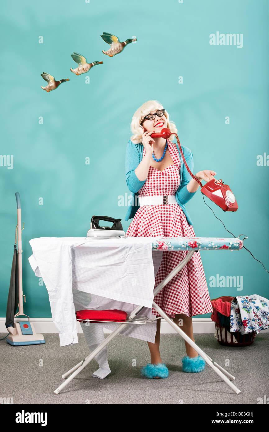 Retro-Bild der 1960er Jahre Hausfrau ein Bügeleisen/-Brett Stockbild