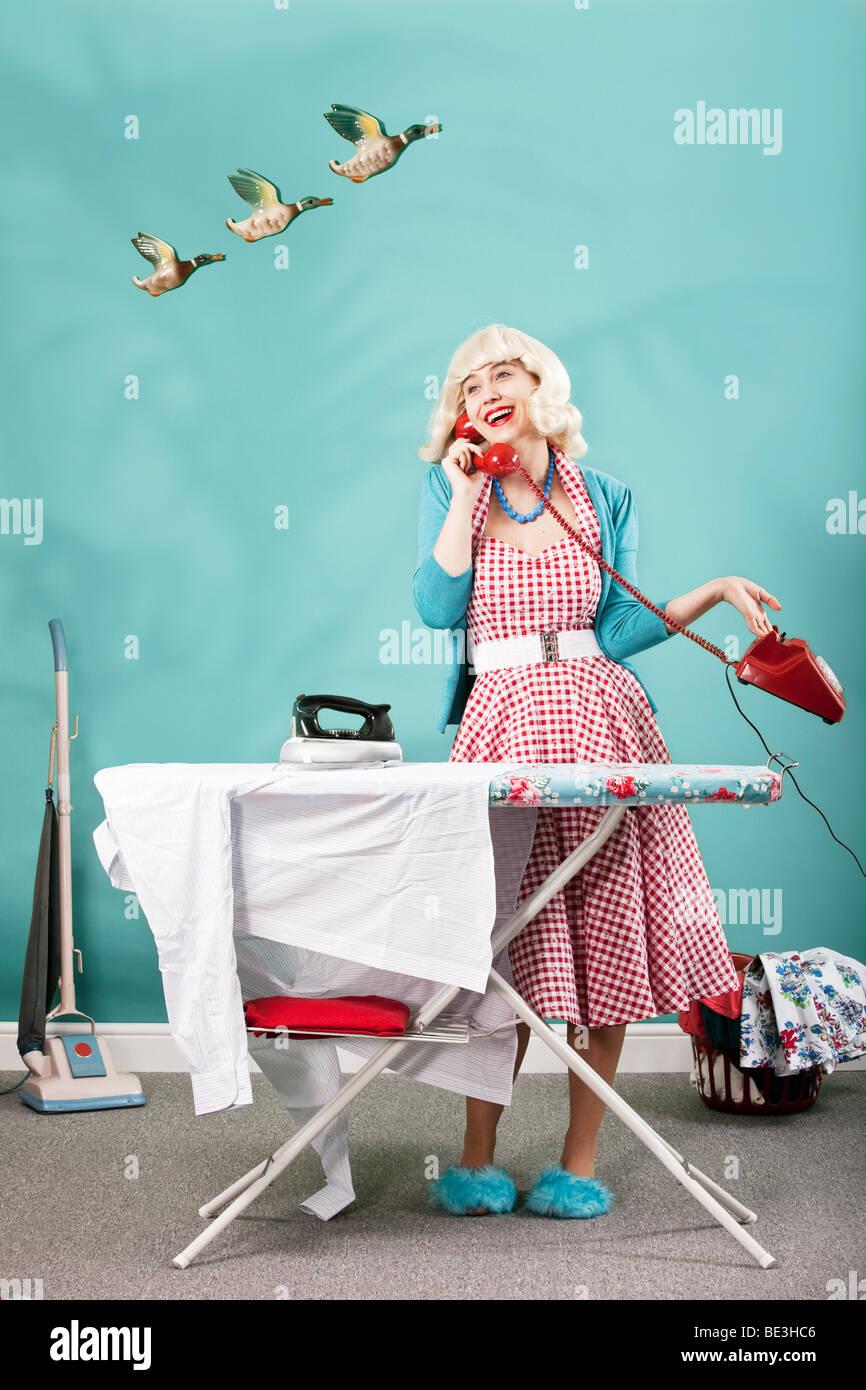 Retro-Bild der 1960er Jahre Hausfrau am Telefon sprechen, während ein Bügeleisen/-Brett Stockbild