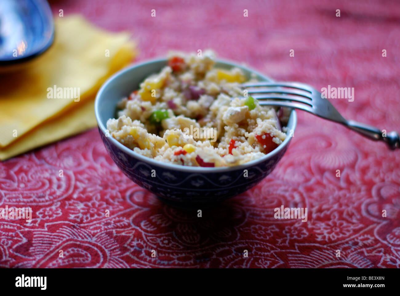 Couscous in blau Schüssel auf roten Tischdecke Stockfoto