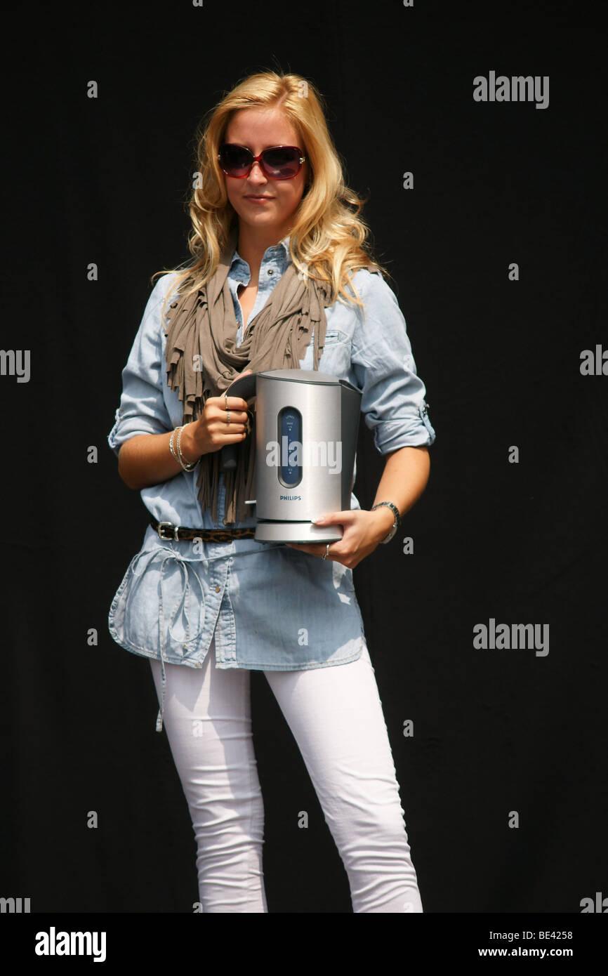 Single-Frau adult Oberkörper Brust Gesicht Modenschau halten Haushaltsgeräte schwarzen Hintergrund im Stockbild