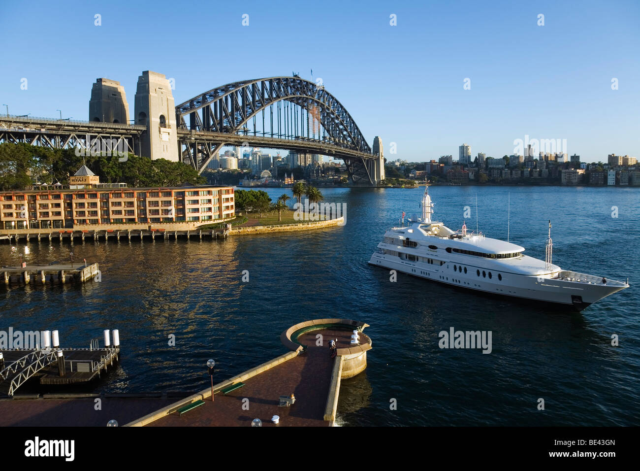 Eine Luxus-Yacht-Motoren in Campbells Cove mit der Sydney Harbour Bridge hinaus. Sydney, New South Wales, Australien Stockbild