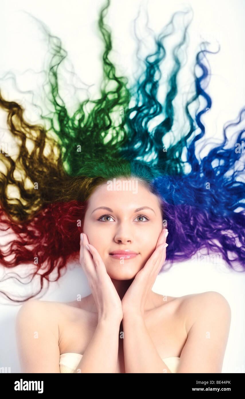 Junge Frau mit langen lockigen Haaren. Regenbogen coloriertes Haar. Stockbild