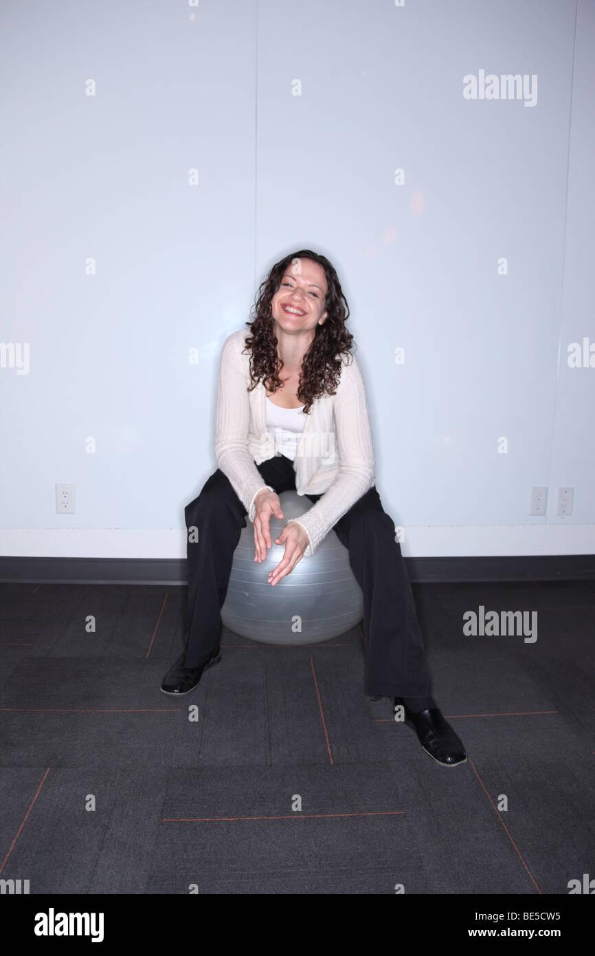 Frau sitzt auf Ball lächelt in die Kamera Stockbild