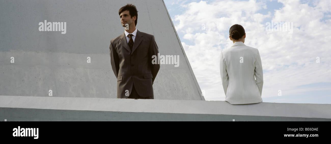 Geschäftsmann, die Aussicht vom Dach, Kollege sitzt auf einem Felsvorsprung in der Nähe Stockbild