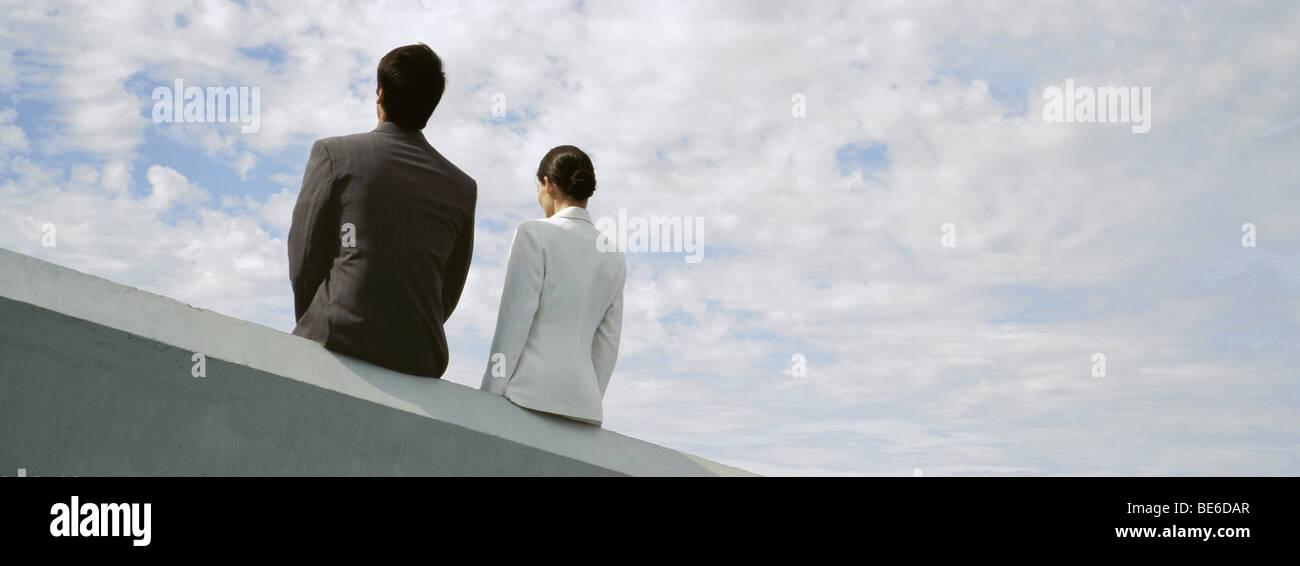 Unternehmer und Unternehmerin sitzen nebeneinander auf Dach Sims Stockbild