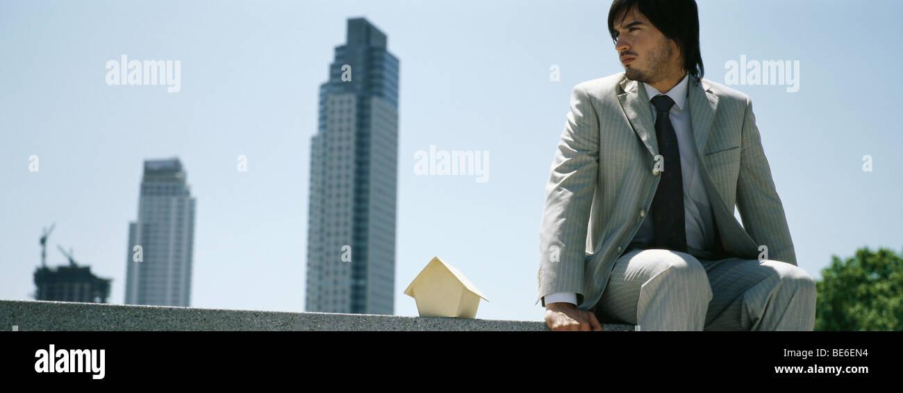 Mann sitzt auf Felsvorsprung neben Miniatur Holzhaus, Wolkenkratzer in Ferne Stockbild