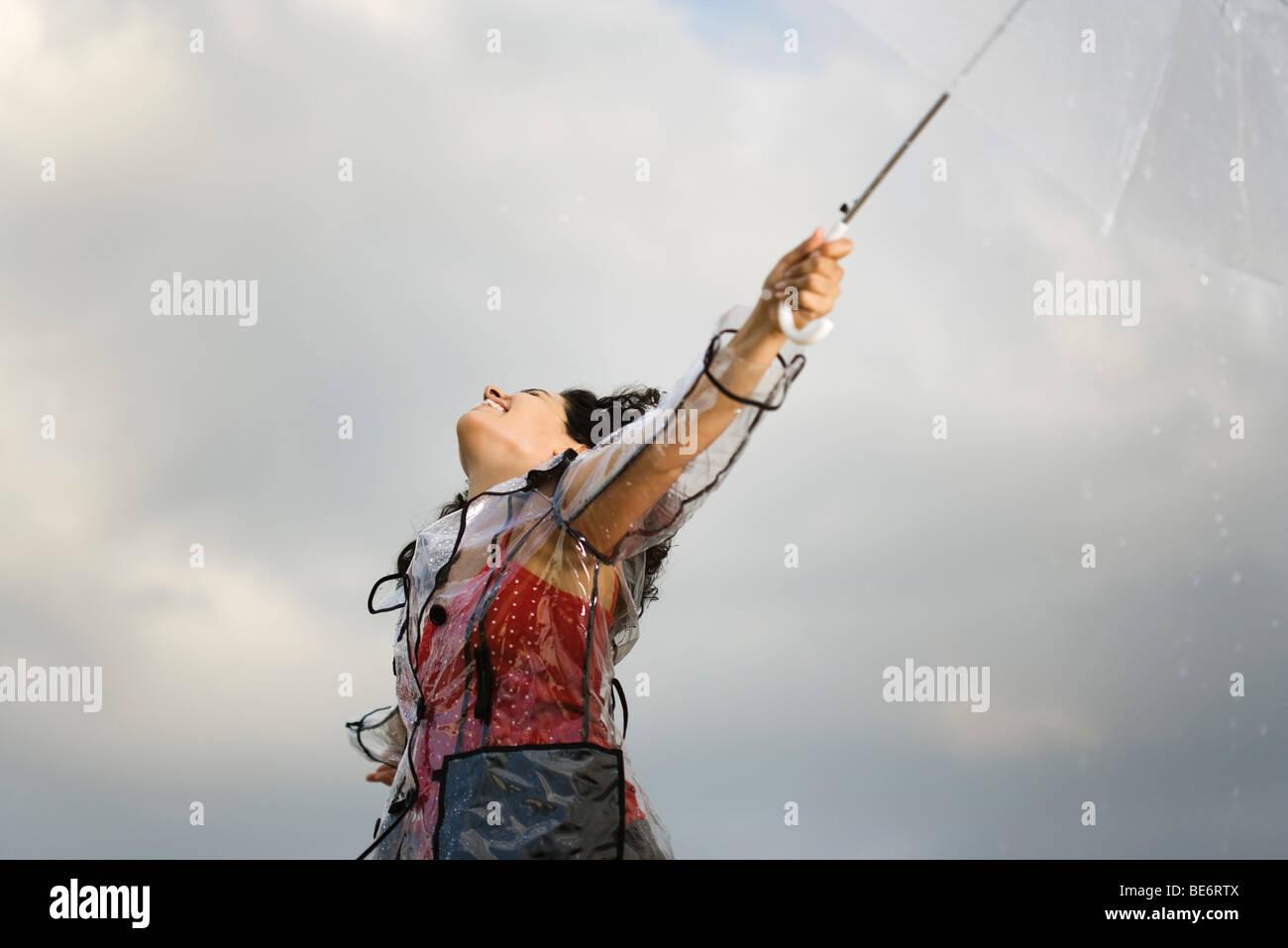 Junge Frau am regnerischen Tag im Freien stehen, so dass Regen fallen auf ihr Gesicht Stockbild