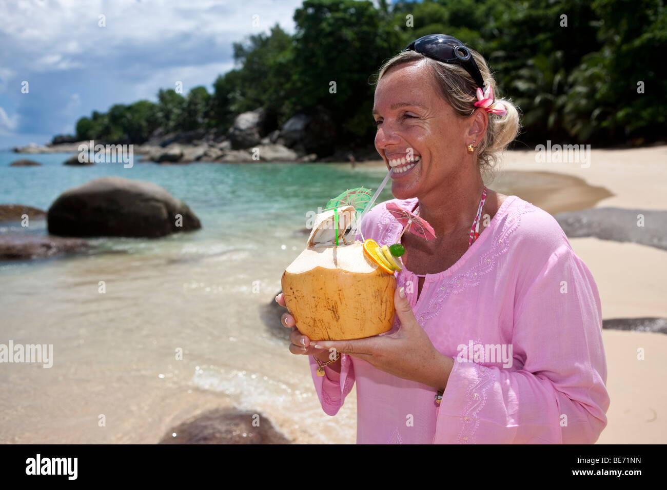 eine frau in einem rosa tunika aus einer dekorierten kokosnuss trinken gef llt mit einem getr nk. Black Bedroom Furniture Sets. Home Design Ideas
