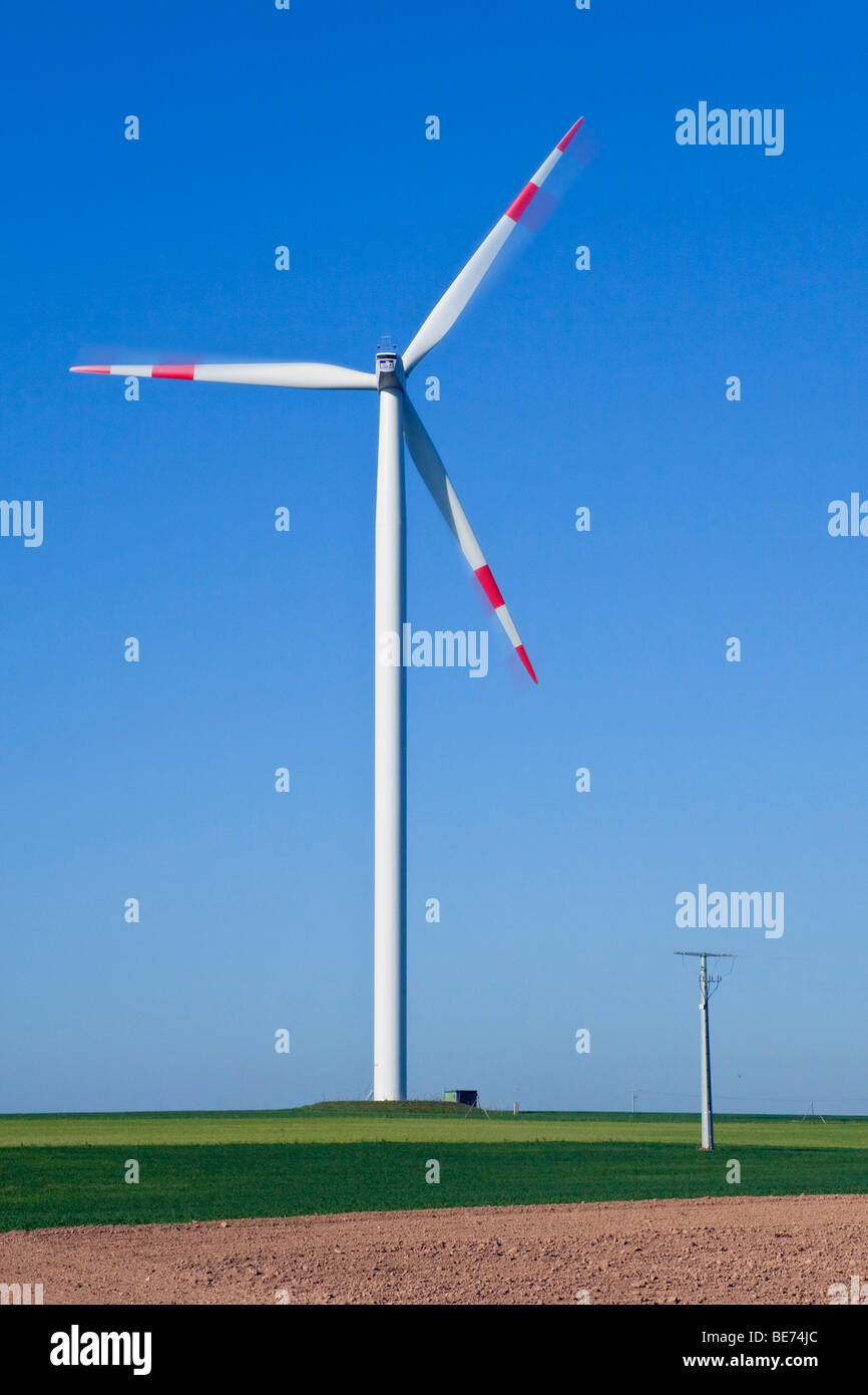 Windkraftanlage vor den Mast einer Übertragungsleitung Stockbild