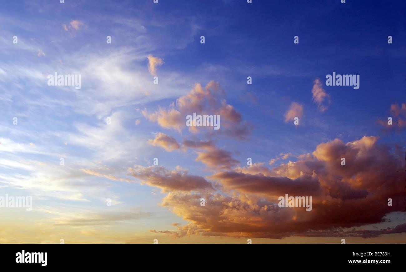blauer Himmel bei Sonnenuntergang, mit weißen und orangefarbenen Wolken Stockbild