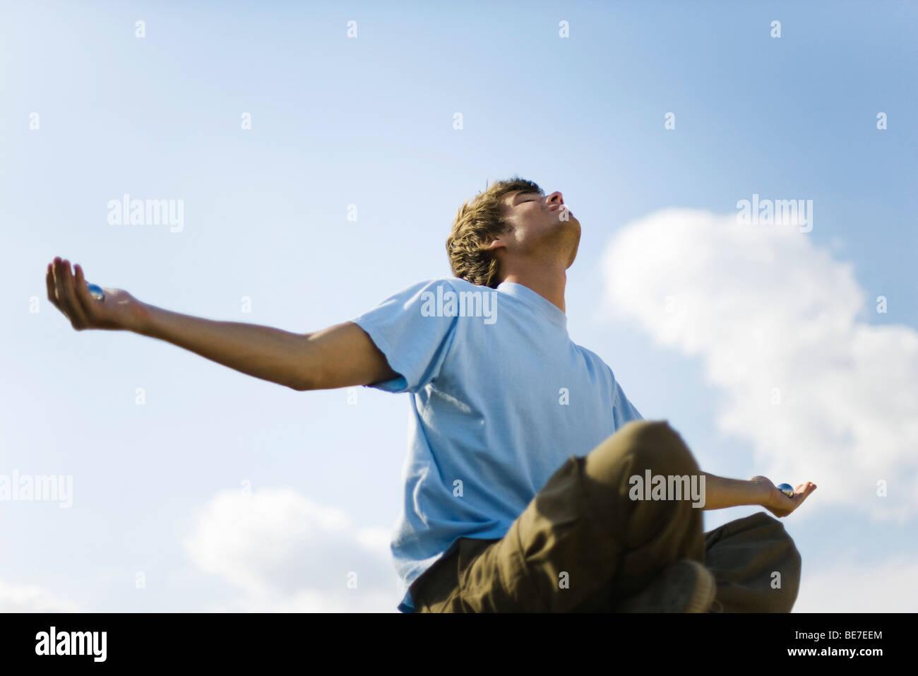 Junger Mann im Freien zu meditieren, hält Yin Yang Kugeln Stockbild