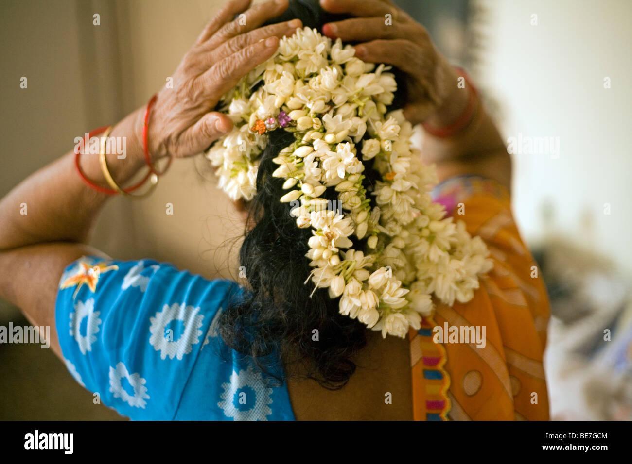 Eine ältere Frau ordnet Blumen im Haar in ihrem Schlafzimmer, Janakpuri, New Delhi, Indien Stockbild