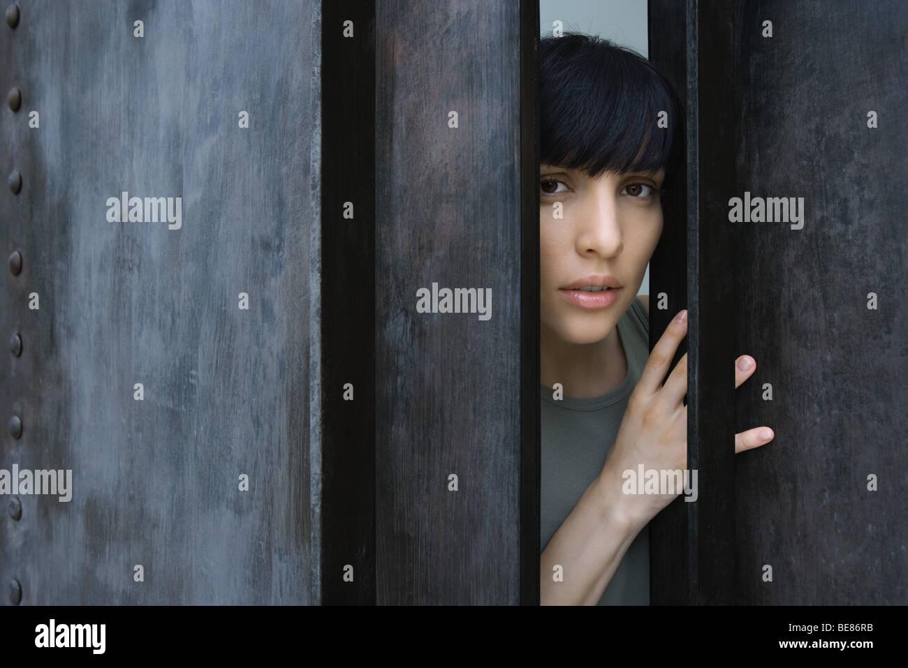 Frau sich öffnende Tür, Blick in die Kamera Stockbild