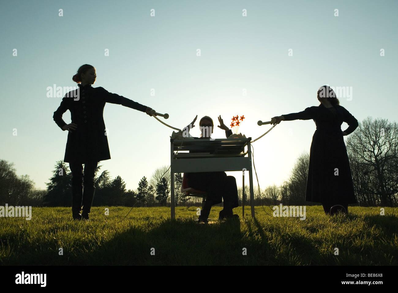 Frau sitzt am Schreibtisch im Feld mit Handzeichen, Weibchen halten, Festnetz-Telefone auf beiden Seiten, Silhouette Stockfoto