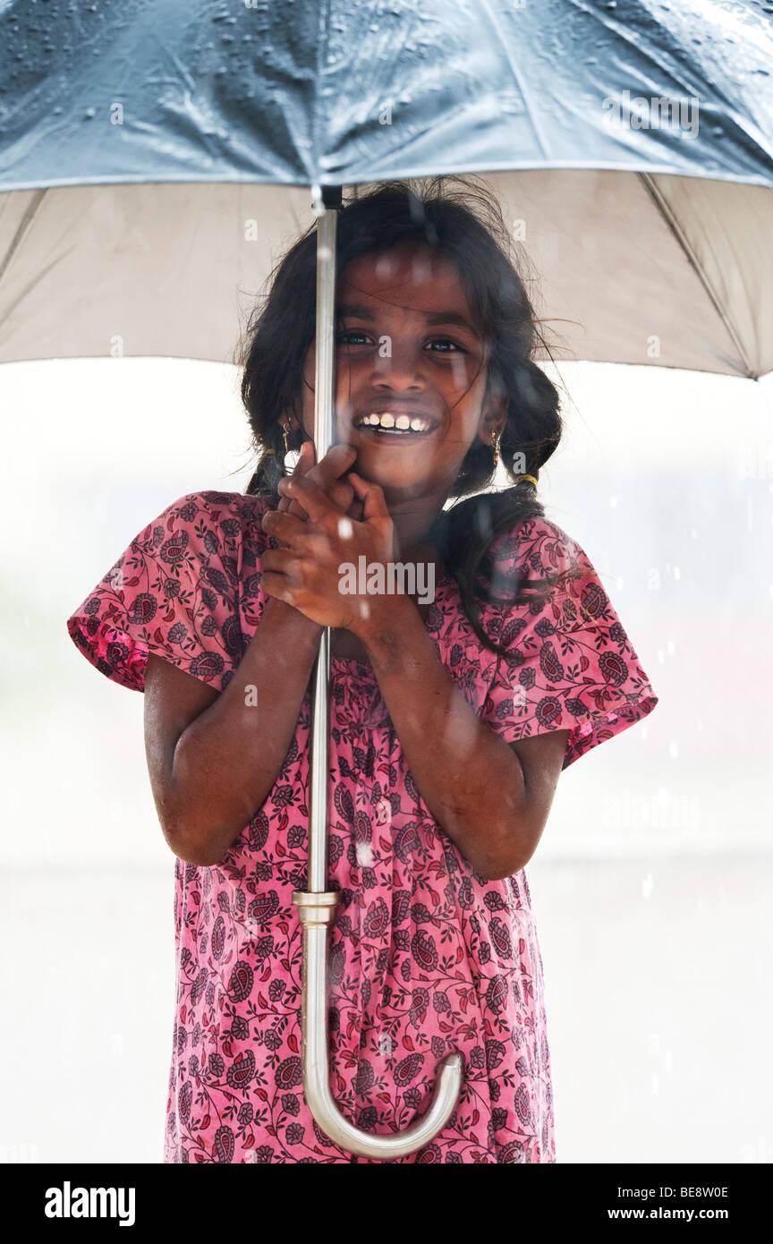 Indische Mädchen unter einem großen Schirm während der Monsunregen Stockbild