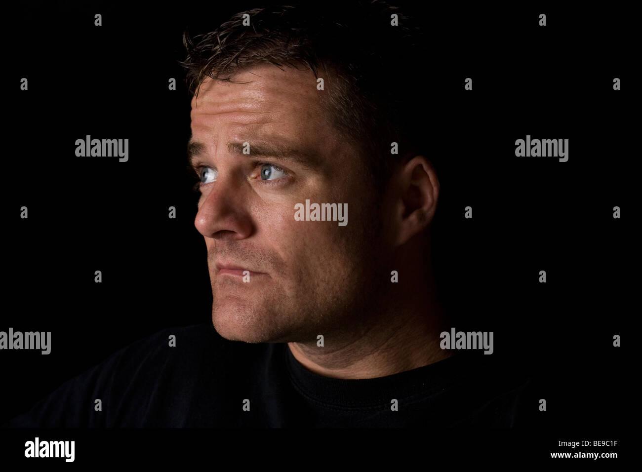 Ein Portrait eines Mannes starrt von der Kamera entfernt Stockbild