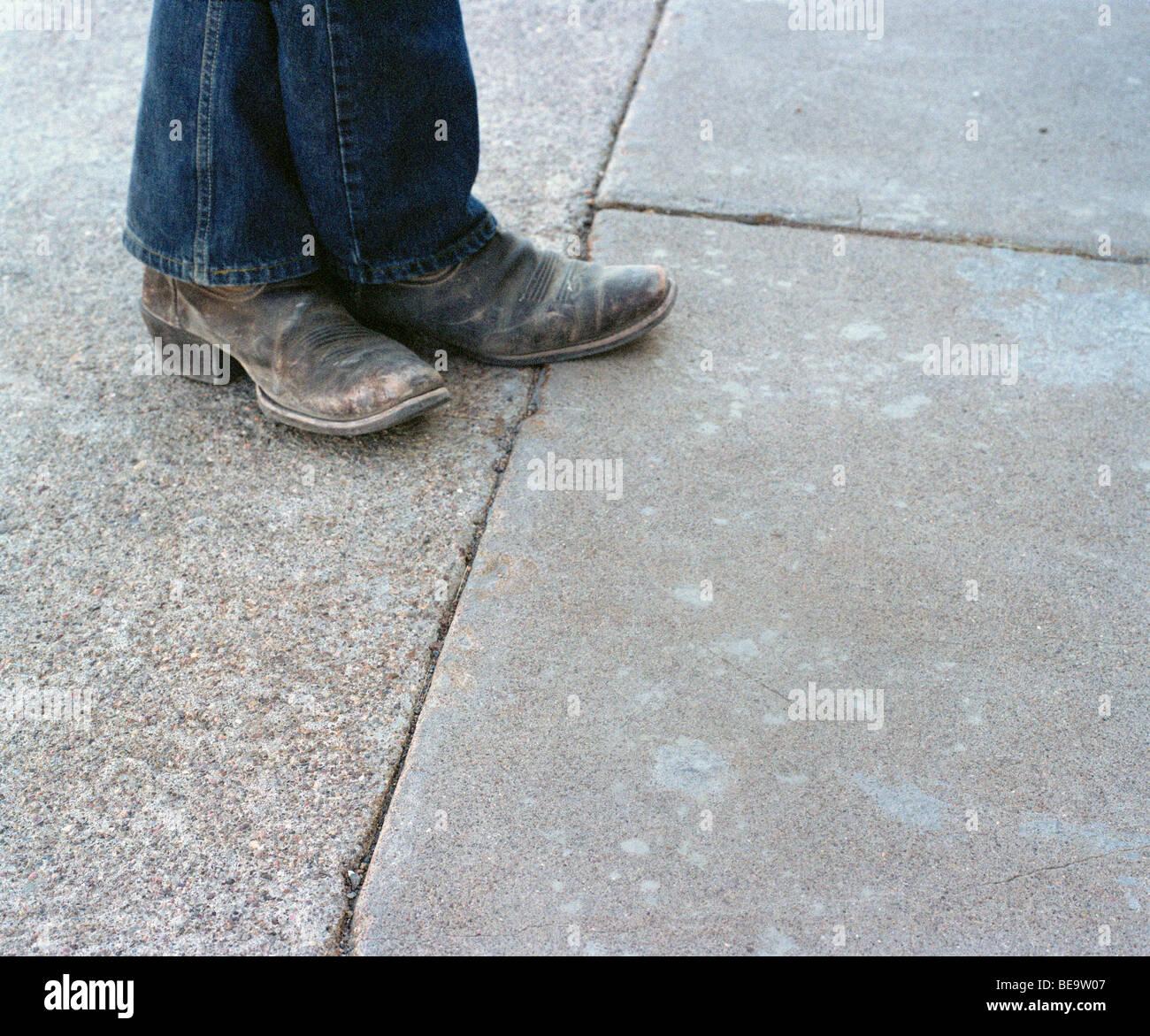 Nahaufnahme von verwitterten Cowboy-Stiefel und jeans Stockbild