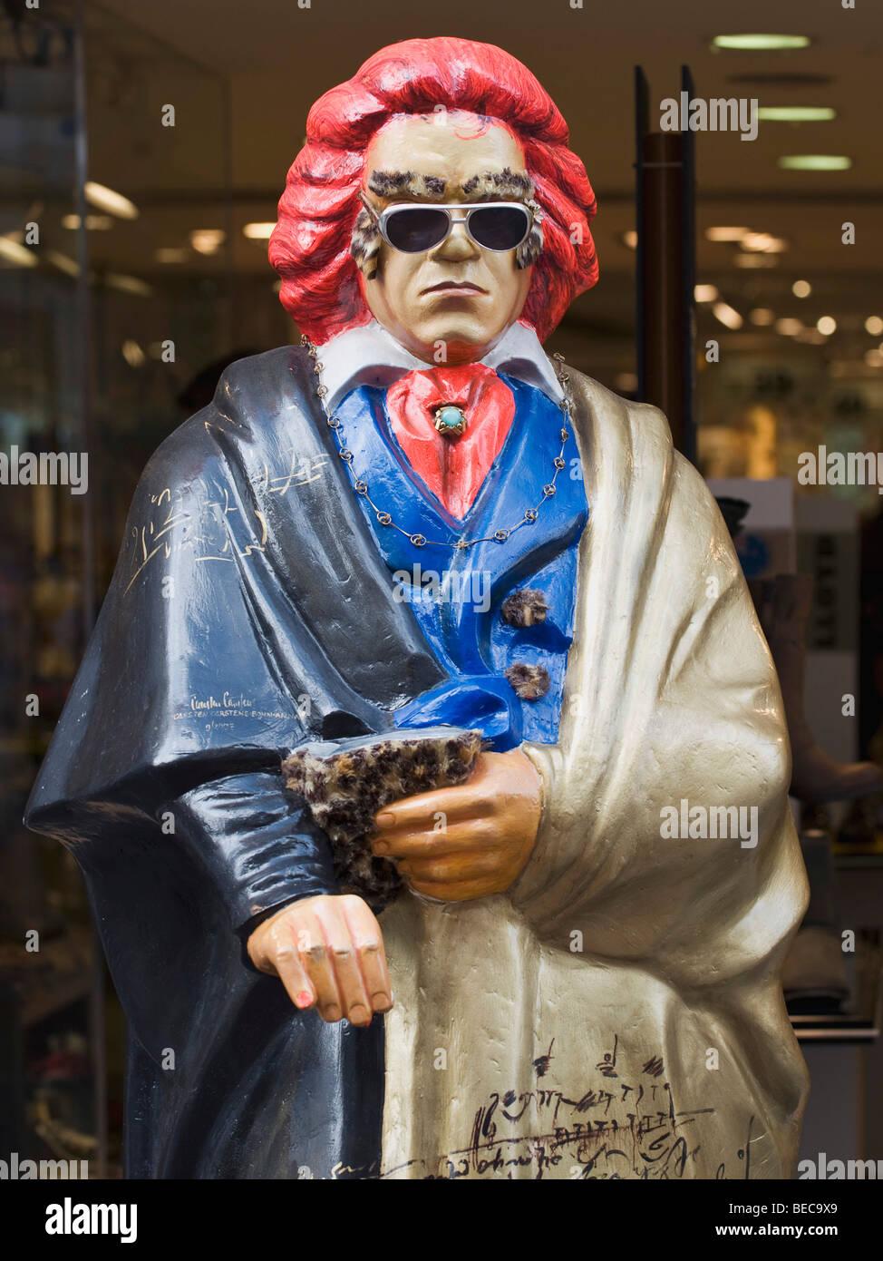 Beethoven-Statue mit roten Haaren, Sonnenbrille und bunte Kleidung vor einer Verkaufsstelle Stockbild