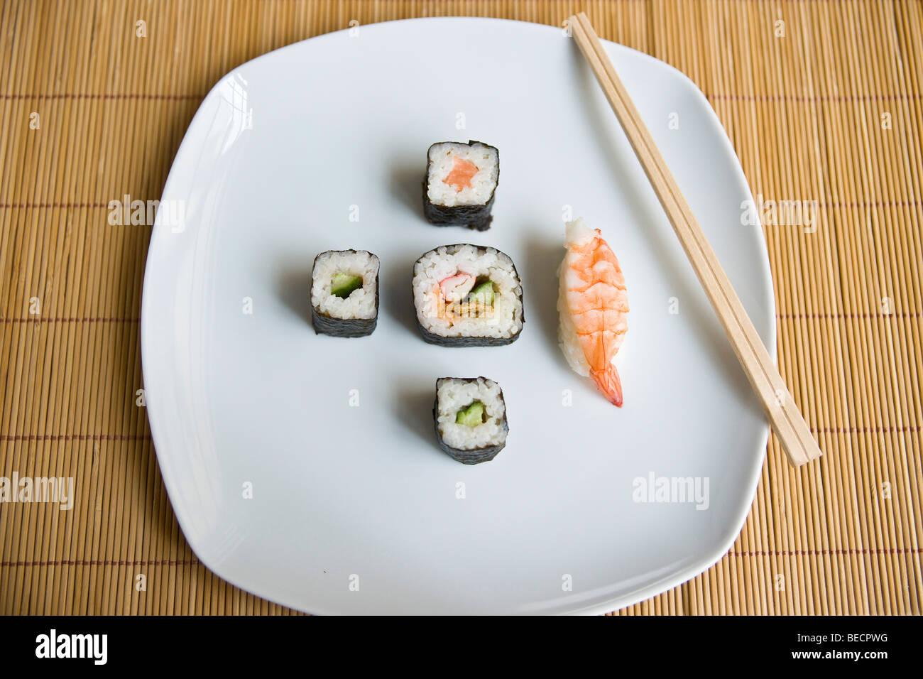 Verschiedene Arten von Sushi und Stäbchen auf dem Teller Stockbild