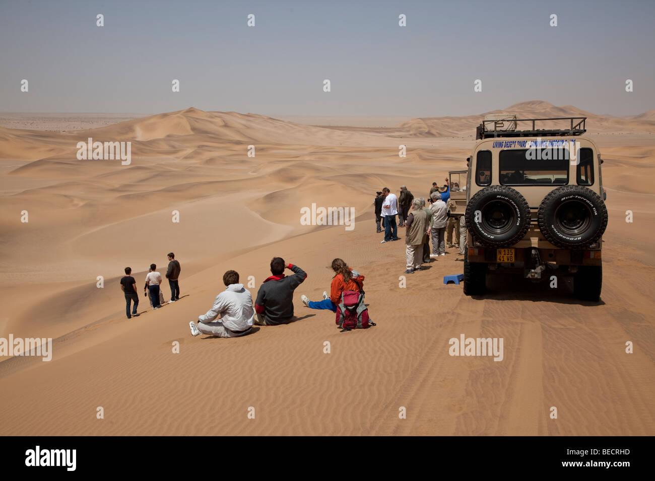 Touristen zwischen Sanddünen in der Nähe von Swakopmund, Namib-Wüste, Namibia, Afrika Stockbild