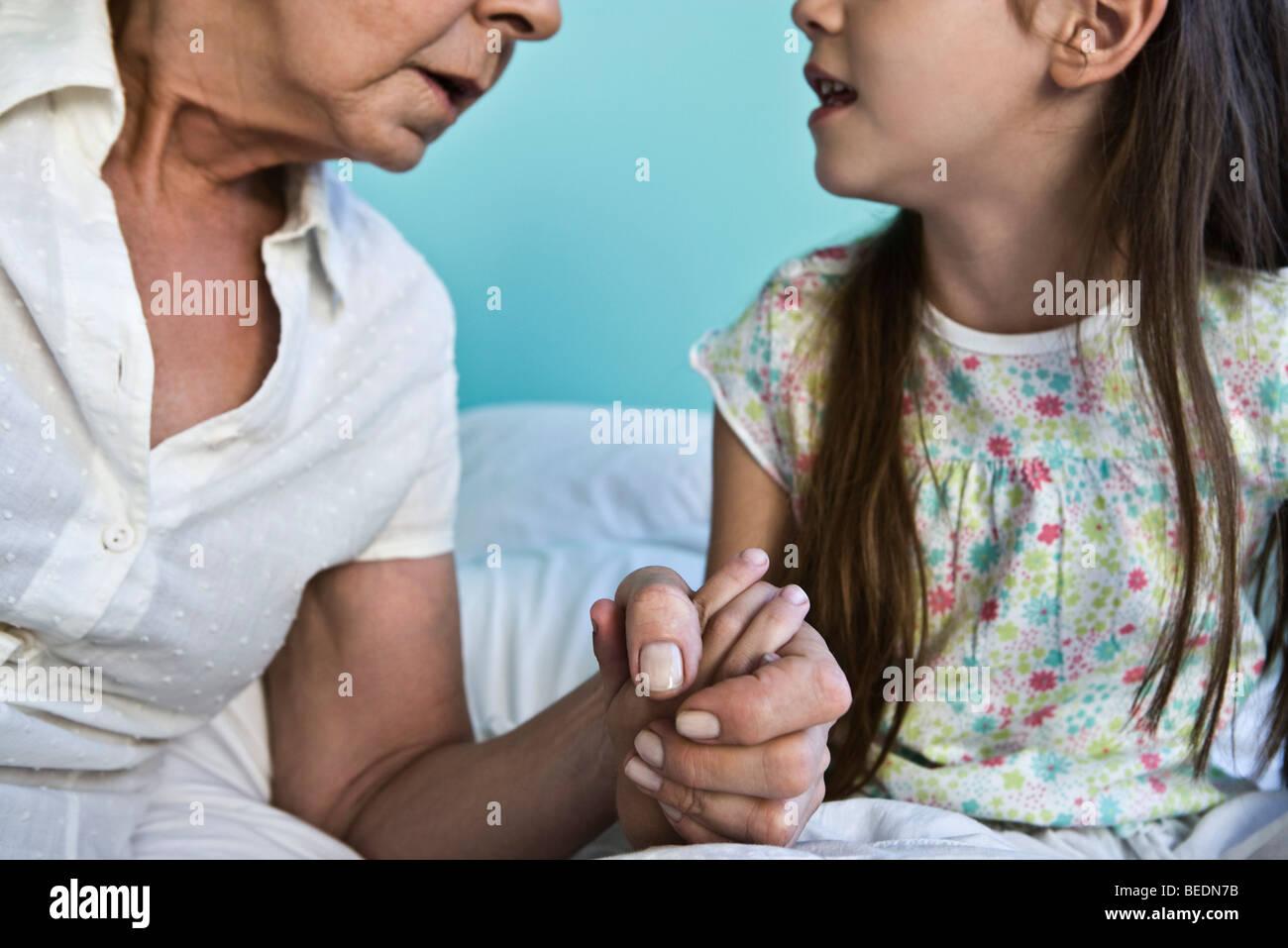 Grossmutter und junge Enkelin Händchenhalten und reden, beschnitten Stockbild