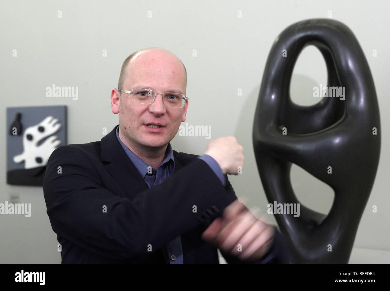 Oliver Kornhoff, Direktor des Arp-Museum Remagen Rolandseck, Bronzeskulptur von Hans Arp an zurück mit dem Stockbild