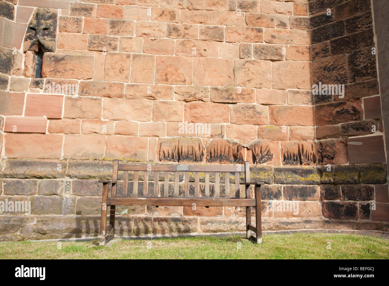 Sitzbank auf dem Rasen vor einer Kirchenmauer Stockbild