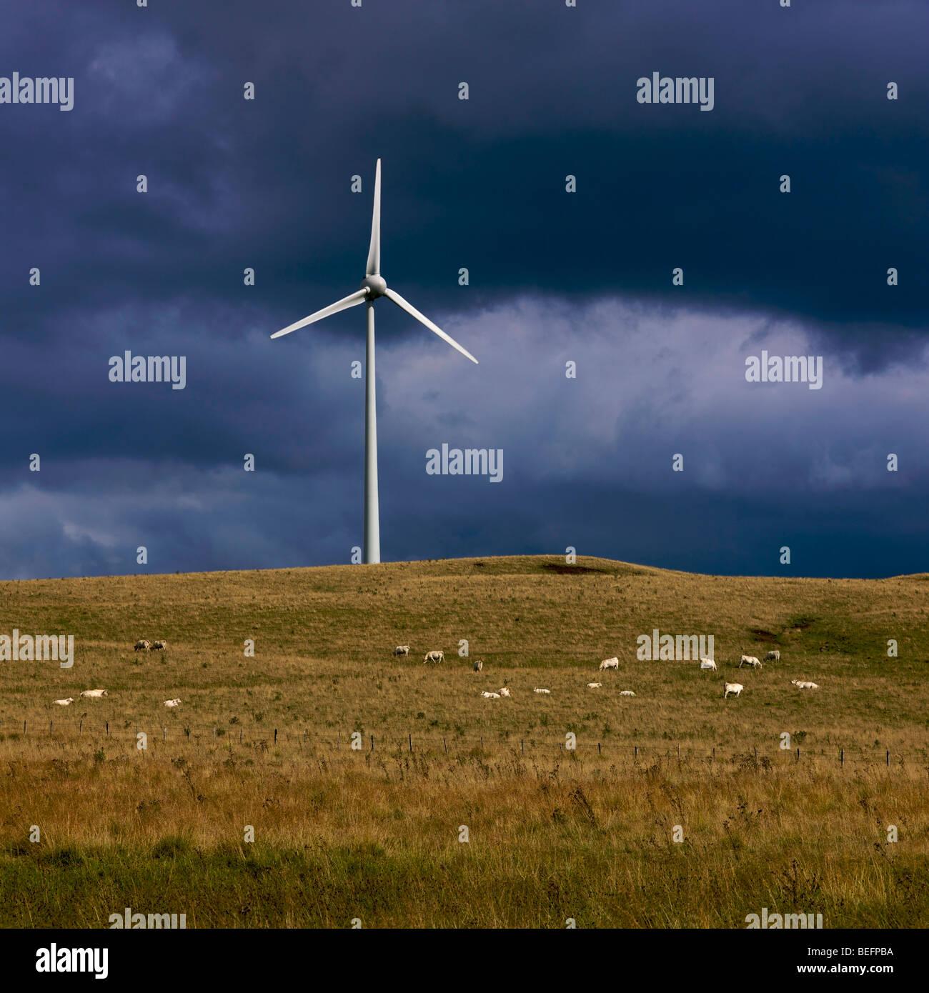 Große Windkraftanlage auf einem Plateau in einer ländlichen Umgebung mit dunklen Gewitterhimmel Stockbild