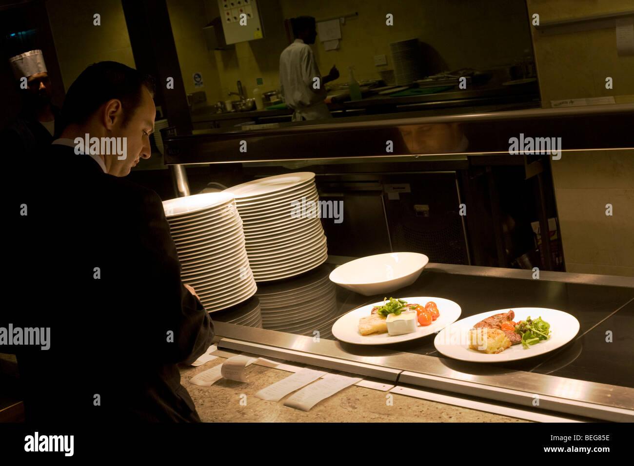 Ein Oberkellner soll fertigen Gerichte beim Service im Flughafen Heathrow Sofitel-Vivre Restaurant zu nehmen. Stockbild