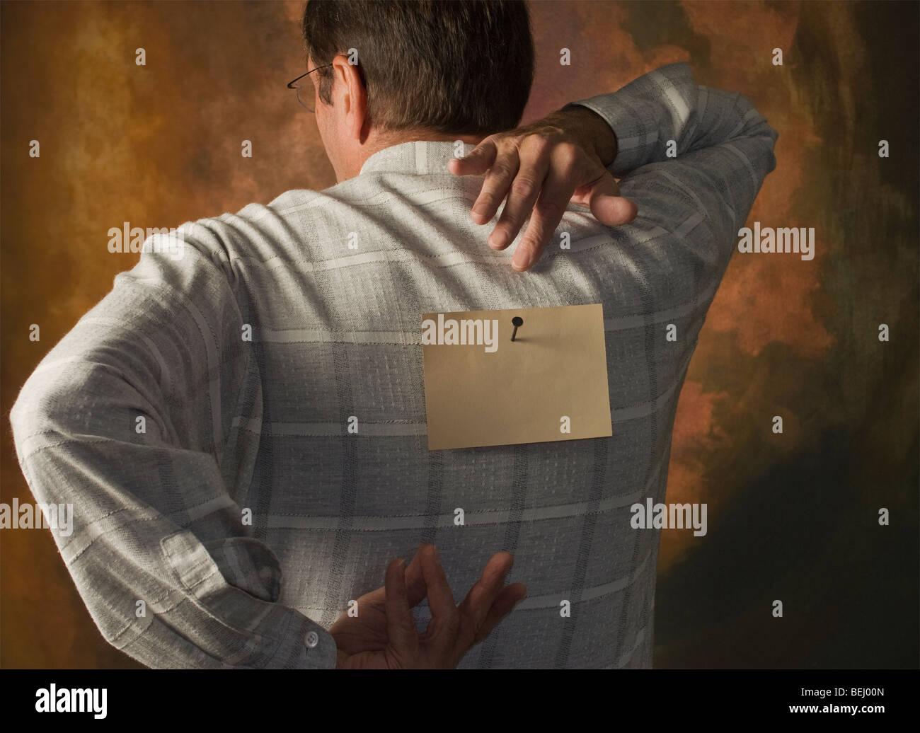 Mann Griff nach Hinweis auf seinem Rücken genagelt Stockbild