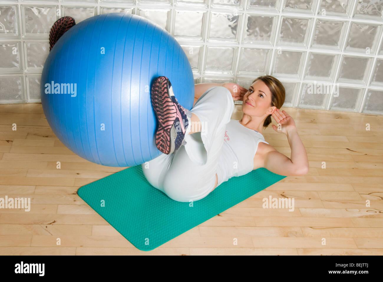 Frau mit Gymnastikball, Zug / in einer Turnhalle trainieren Stockbild