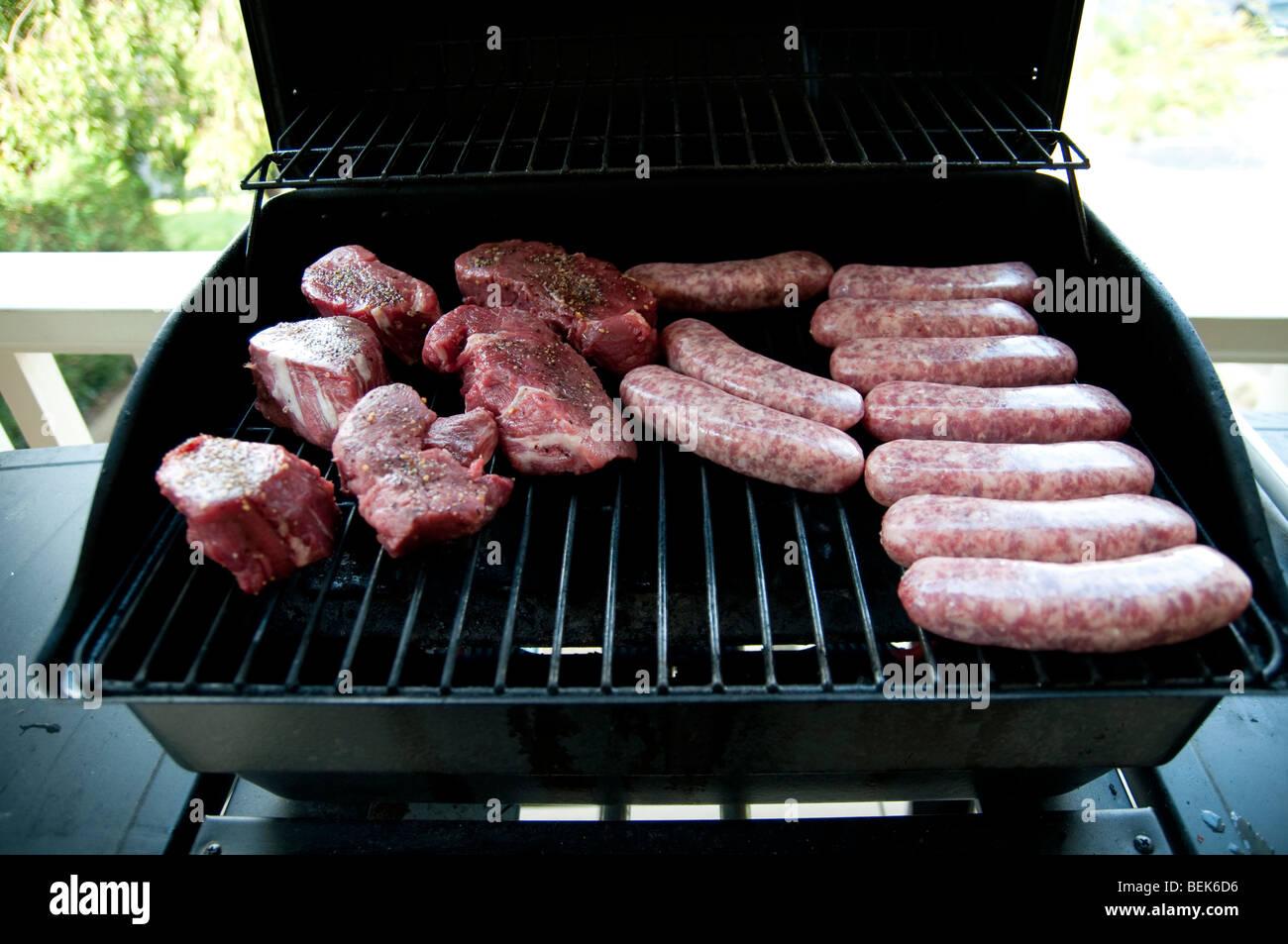 Erfahrene rohes Steak Koteletts auf einem BBQ-Grill Stockbild